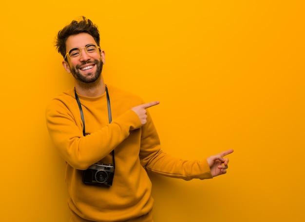 Junger fotografmann, der auf die seite mit dem finger zeigt