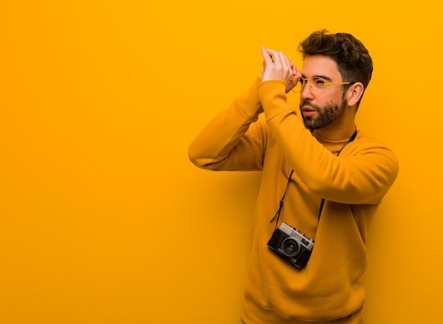 Junger fotografmann, der die geste eines fernglases macht