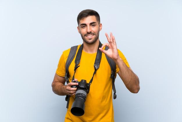Junger fotografmann, der ein okayzeichen mit den fingern zeigt