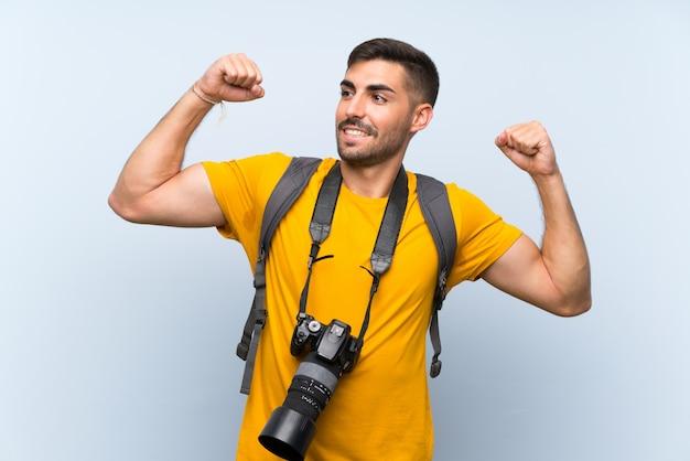 Junger fotografmann, der einen sieg feiert