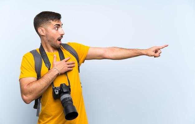 Junger fotografmann, der finger auf die seite zeigt