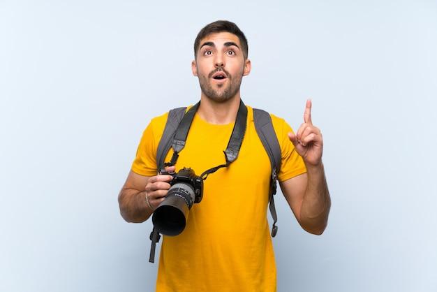 Junger fotografmann, der mit dem zeigefinger eine großartige idee zeigt