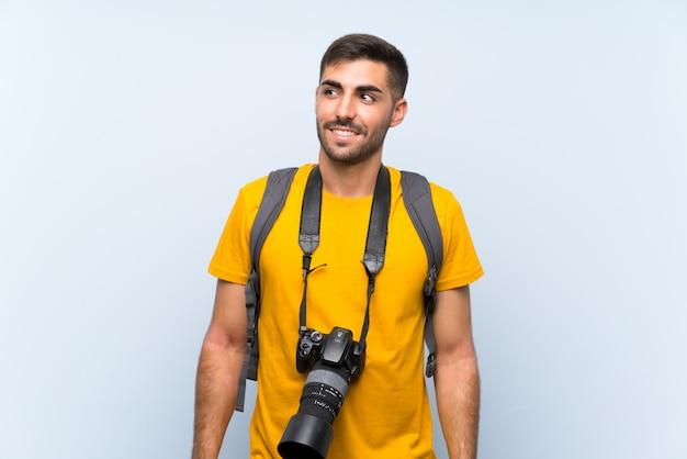 Junger fotografmann, der oben lacht und schaut