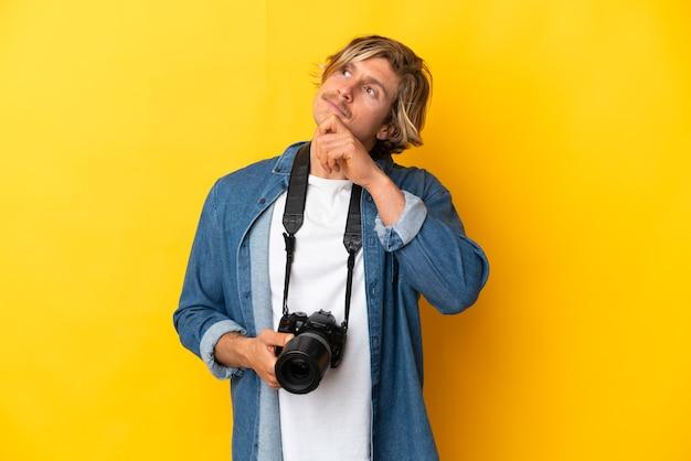 Junger fotografmann lokalisiert auf gelber wand und schaut nach oben