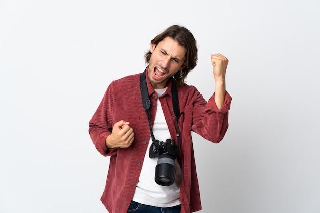 Junger fotografmann lokalisiert auf weißem hintergrund, der einen sieg feiert