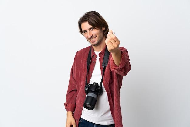 Junger fotografmann lokalisiert auf weißem hintergrund, der geldgeste macht
