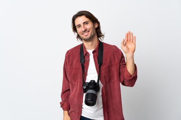 Junger fotografmann lokalisiert auf weißem hintergrund, der mit hand mit glücklichem ausdruck salutiert