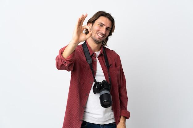 Junger fotografmann lokalisiert auf weißem hintergrund, der ok zeichen mit den fingern zeigt