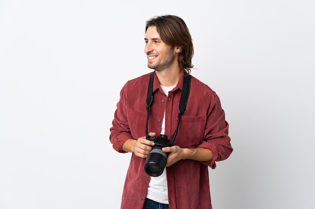 Junger fotografmann lokalisiert auf weißem hintergrund, der seite schaut