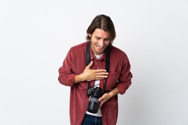Junger fotografmann lokalisiert auf weißem hintergrund, der viel lächelt