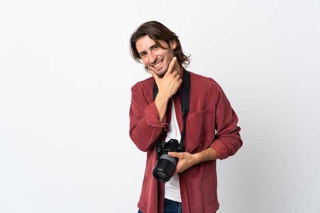 Junger fotografmann lokalisiert auf weißem hintergrund glücklich und lächelnd