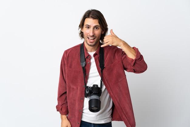 Junger fotografmann lokalisiert auf weißer wand, die telefongeste macht. rufen sie mich zurück zeichen