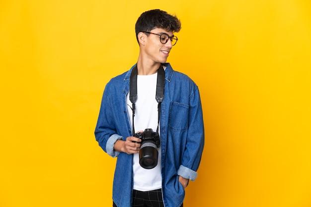 Junger fotografmann über isoliertem gelbem hintergrund, der seite schaut