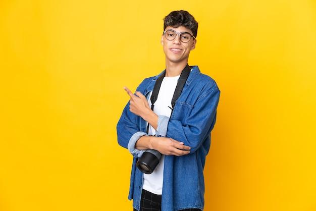 Junger fotografmann über lokalisiertem gelbem hintergrund, der finger zur seite zeigt