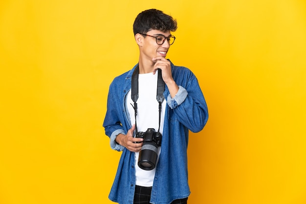 Junger fotografmann über lokalisiertem gelbem hintergrund, der zur seite schaut und lächelt
