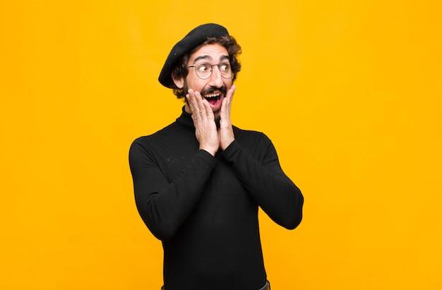 Junger französischer künstlermann, der glücklich, aufgeregt und überrascht fühlt und mit beiden händen auf gesicht gegen orange wand zur seite schaut