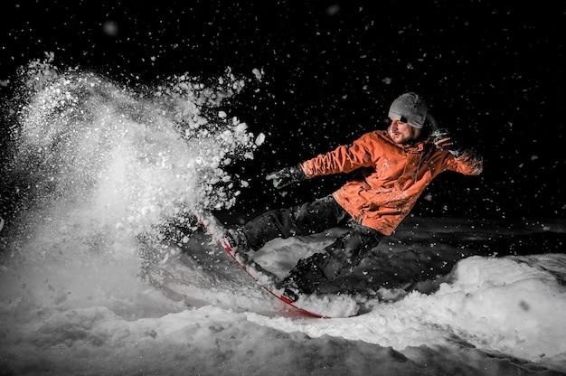Junger freeride snowboarder, der in schnee nachts springt