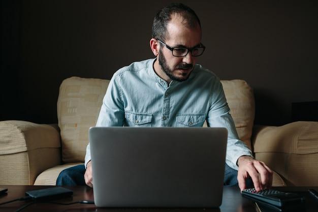 Junger freiberufler, der auf dem sofa sitzt und von zu hause aus arbeitet. telearbeit, telearbeit und telearbeitskonzept.