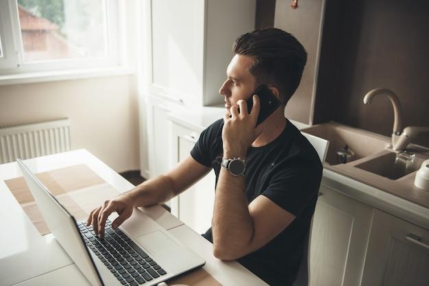 Junger freiberufler, der von zu hause in der küche am laptop arbeitet und am telefon bespricht