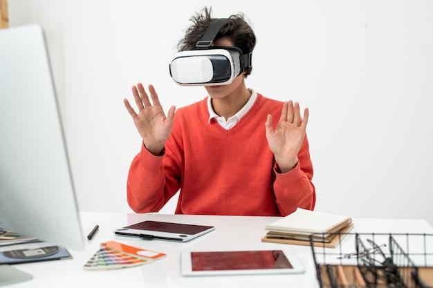 Junger freiberufler im vr-headset, der am schreibtisch sitzt und die virtuelle anzeige vor ihm berührt, während er in einer anderen realität arbeitet