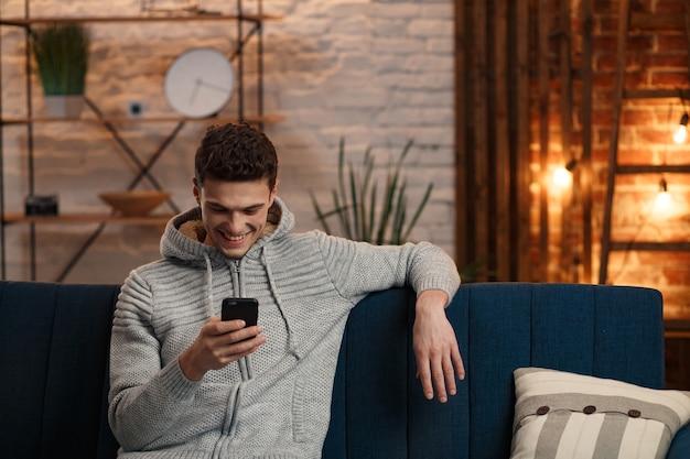 Junger freiberufler mit smartphone und lächeln.