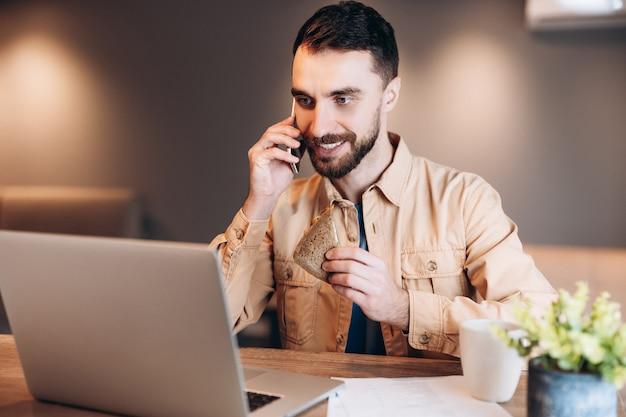 Junger freiberuflicher mann glücklich mit einem telefonanruf