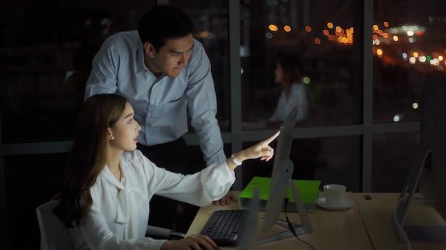 Junger freiberuflicher unternehmer, der spät in der nacht vor dem computer im büro sowohl lächelnd als auch glücklich mit dem neuen geschäft arbeitet. arbeiten spät in der nacht und überstunden konzept