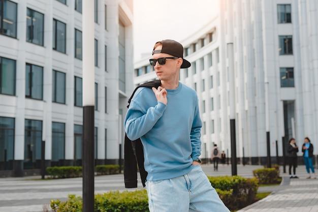 Junger freier, schöner modischer hipster-typ, der die straße hinuntergeht und eine mütze mit sonnenbrille trägt.