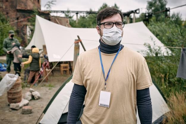 Junger freiwilliger in schutzmaske, der im flüchtlingslager steht