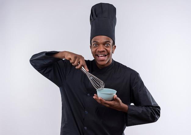 Junger freudiger afroamerikanischer koch in der kochuniform hält schüssel und schneebesen lokalisiert auf weißer wand