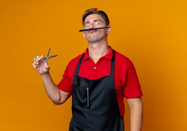 Junger freudiger blonder männlicher friseur in der uniform hält schere und schnurrbart mit kamm lokalisiert auf orange raum mit kopienraum