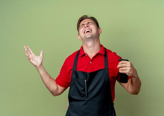 Junger freudiger blonder männlicher friseur in der uniform hält sprühflasche und erhebt hand, die lokal auf olivgrünem raum mit kopienraum nach oben schaut