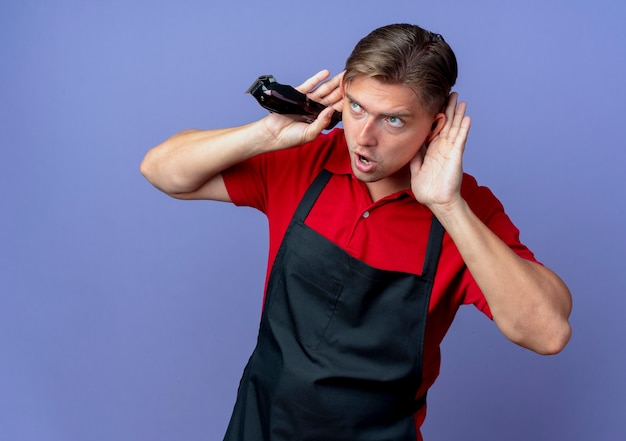 Junger freudiger blonder männlicher friseur in uniform setzt hände hinter ohren, die seite betrachten, die haarschneidemaschine lokalisiert auf violettem raum mit kopienraum hält