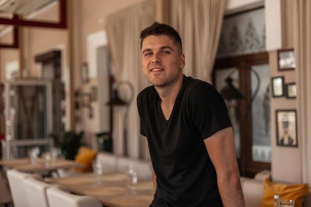 Junger freudiger hübscher mann mit einem niedlichen lächeln in einem modischen schwarzen t-shirt mit einer stilvollen frisur ruht in einem vintagen café in der stadt.