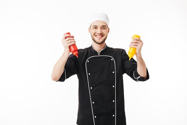 Junger freudiger männlicher koch in der schwarzen uniform, die flaschen senf und ketchup in den händen glücklich hält