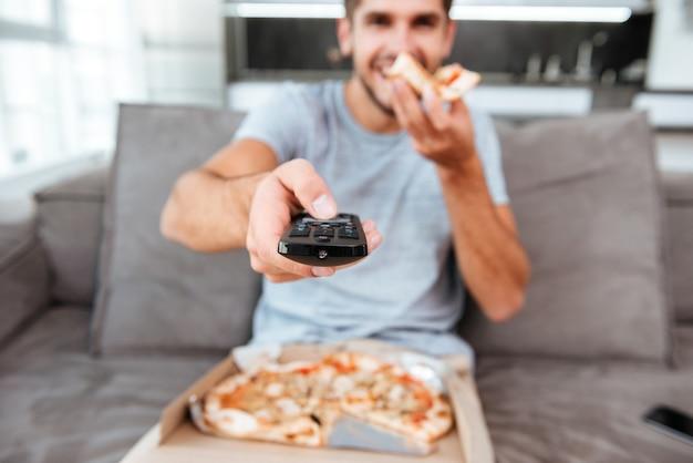 Junger freudiger mann, der fernbedienung hält und den knopf drückt, während pizza isst. fokus auf fernbedienung.