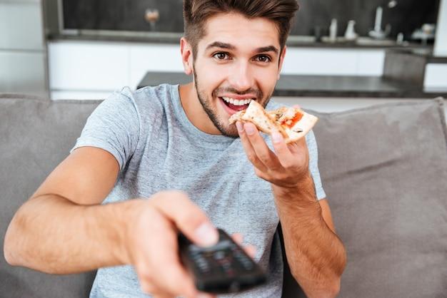 Junger freudiger mann, der fernbedienung hält und den knopf drückt, während pizza isst.