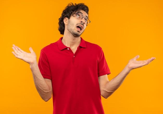 Junger freudiger mann im roten hemd mit optischer brille hält hände offen lokalisiert auf orange wand