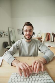Junger freundlicher bediener mit headset, der auf computertastatur tippt, während er am tisch vor monitor sitzt und kunden online berät