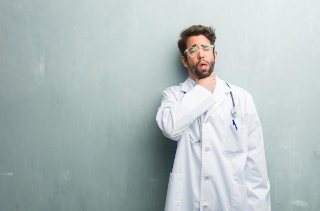 Junger freundlicher doktormann gegen eine grunge wand mit einem kopienraum besorgt und überwältigt