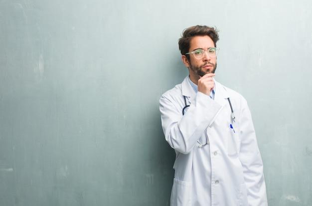 Junger freundlicher doktormann gegen eine grunge wand mit einem kopienraum oben denkend und schauend