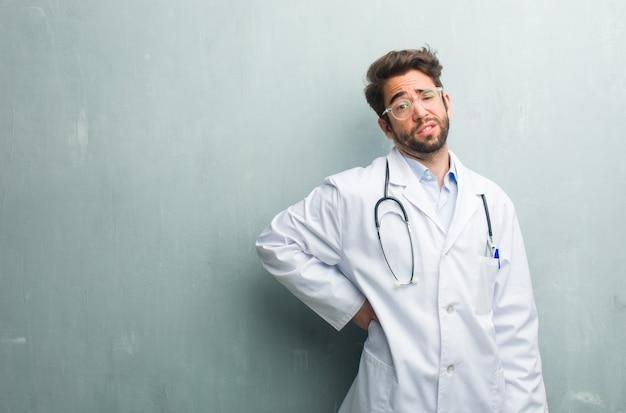 Junger freundlicher doktormann gegen eine schmutzwand mit einem kopienraum mit den rückseitigen schmerz wegen des arbeitsdruckes, müde und klug