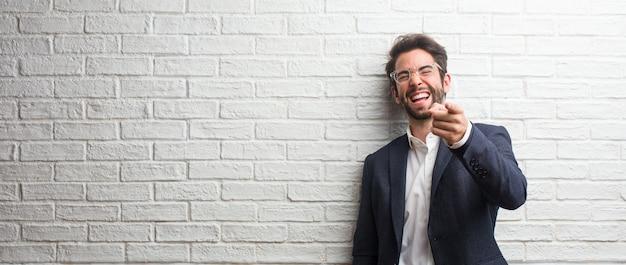 Junger freundlicher geschäftsmann, der über anderen schreit, lacht und sich lustig macht