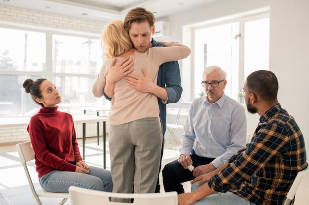 Junger freundlicher mann, der reife blonde frau unterstützt, während sie umarmung bei psychologischer therapiesitzung gibt