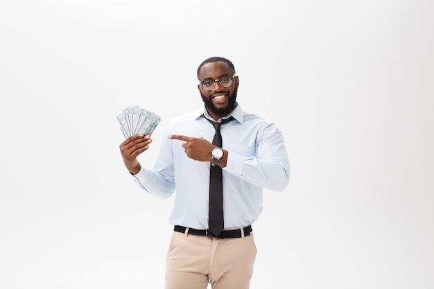Junger freundlicher schwarzer geschäftsmann, der auf das geld lokalisiert auf weiß hält und zeigt