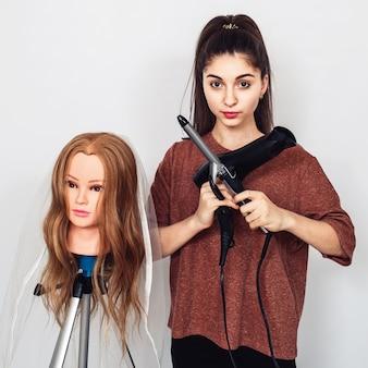 Junger friseur mit lockenstab, fön und mannequinkopf auf stativ. Premium Fotos