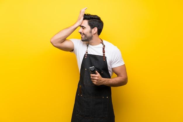 Junger friseurmann über lokalisiertem gelb hat etwas verwirklicht und die lösung beabsichtigt