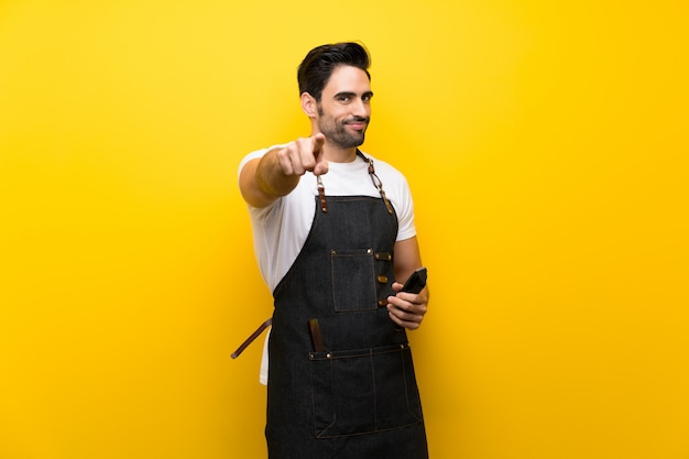 Junger friseurmann über lokalisiertem gelbem hintergrund zeigt finger auf sie mit einem überzeugten ausdruck