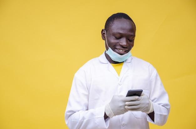 Junger fröhlicher afrikanischer arzt, der auf seinem telefon an der gelben wand tippt