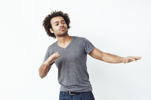 Junger fröhlicher afrikanischer mann, der tanz bewegt.